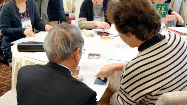 お見合い会で、子どもの身上書を見せ合いながら話す参加者=東京大神宮(画像の一部を加工しています)