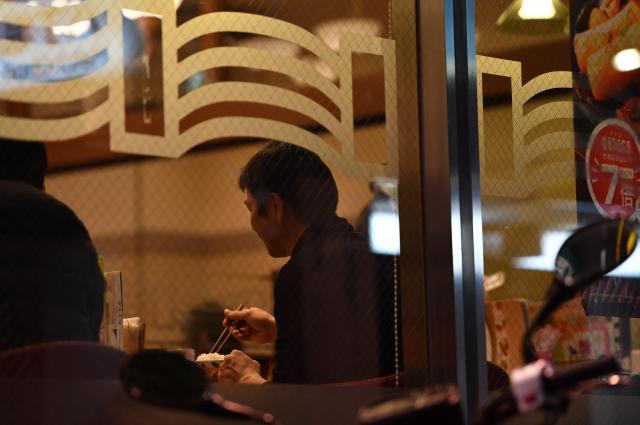 ファミレスで1人夕食をとる男性。妻と子どもがいる自宅には自室がないため、試験勉強をするために来たという=東京都中央区、北村玲奈撮影