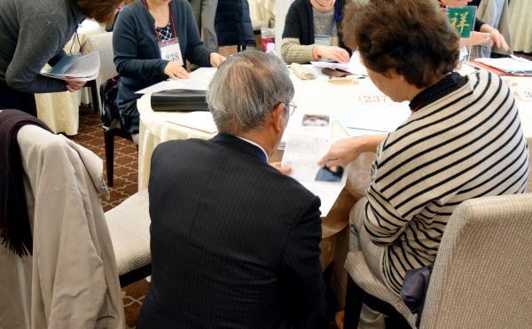 【代理婚活】お見合い会で、子どもの身上書を見せ合いながら話す参加者=東京大神宮(画像の一部を加工しています)