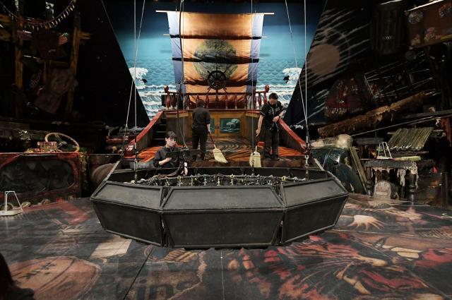 天井から降りる大きな照明の輪。奥には昔ながらのほうきで舞台をきれいに掃除するスタッフ。