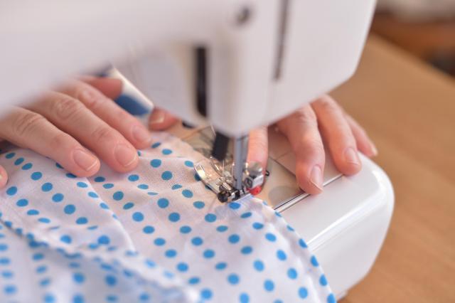 新しいお弁当袋をミシンで縫う女性=滝沢美穂子撮影