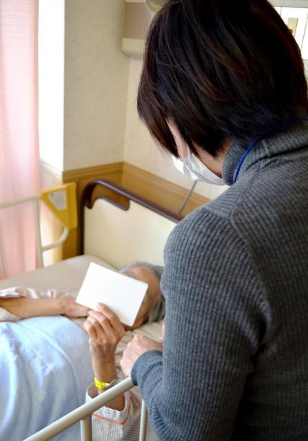 療養病床にいる母(81)を見舞う女性(49)。受験を控えて来られない娘の写真を持ってきた=東京都内