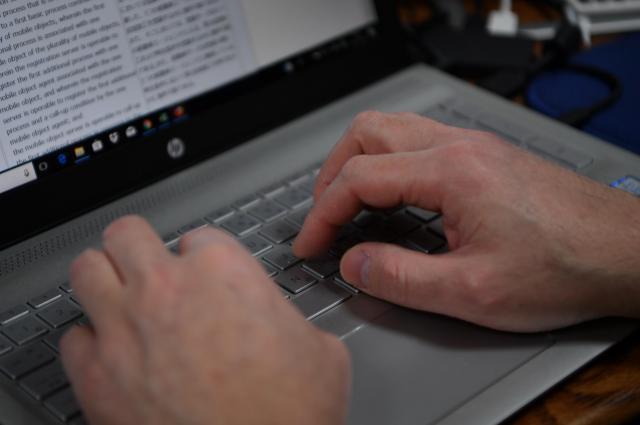 自宅のパソコンで翻訳をする男性の手元=北村玲奈撮影