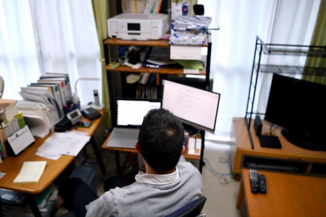 翻訳の仕事に使用するパソコンのモニターを見つめる男性=北村玲奈撮影