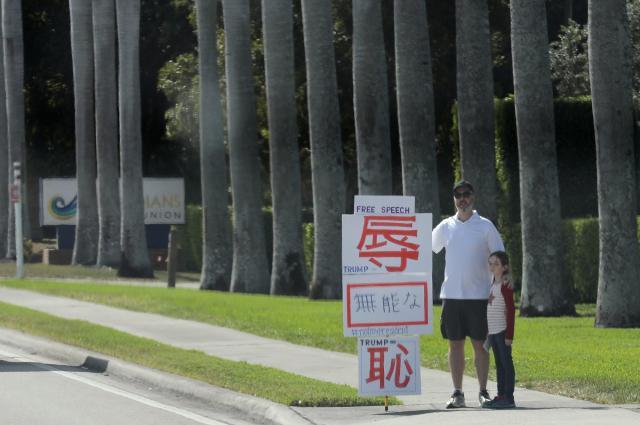 訪米した安倍首相がトランプ大統領とゴルフ場を訪れる際、通り沿いにプラカードを持って抗議する人。日本語で「恥辱」「無能」と書かれている=2017年2月、アメリカ・フロリダ州