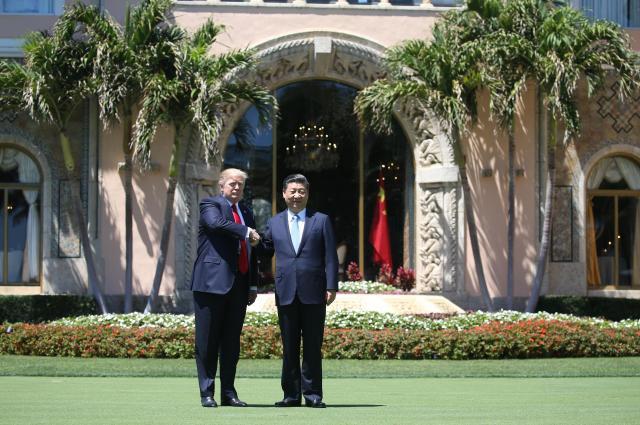 トランプ氏の別荘「マール・ア・ラーゴ」で、握手をするトランプ氏(左)と中国の習近平国家主席=2017年4月、アメリカ・フロリダ州