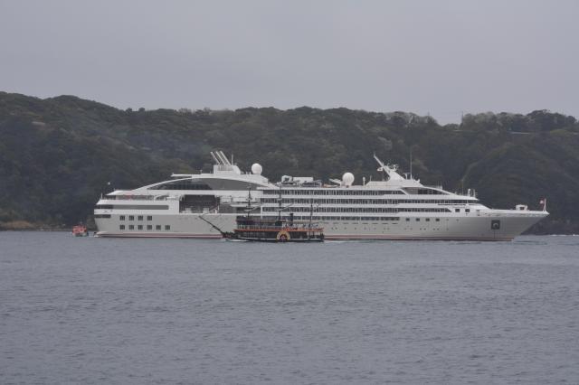 下田港に寄港した豪華客船ル・ソレアル。手前を、黒船を模した遊覧船が横切った=下田市の下田港、2016年4月