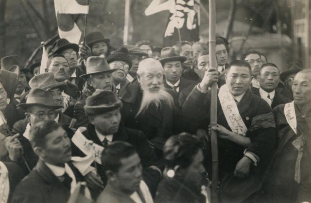 1923年、東京で行われた普通選挙を求めるデモで終点の坂本公園(現・坂本町公園)で、閉会を宣言する自由民権運動の闘士・河野広中(中央の老人)と尾崎行雄(その左)