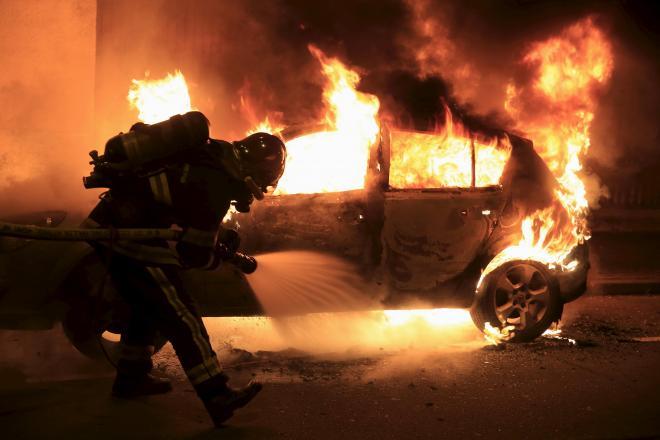 フランス北部リールで燃えさかる車両の消火活動にあたる消防隊員=2016年1月1日