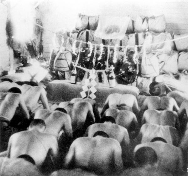 1942年2月のパレンバン攻撃への出発前、神酒をそなえ「無事開傘と必勝」を祈願する日本陸軍落下傘部隊の隊員=朝日新聞社発行「大東亜戦争写真全輯第1巻」より