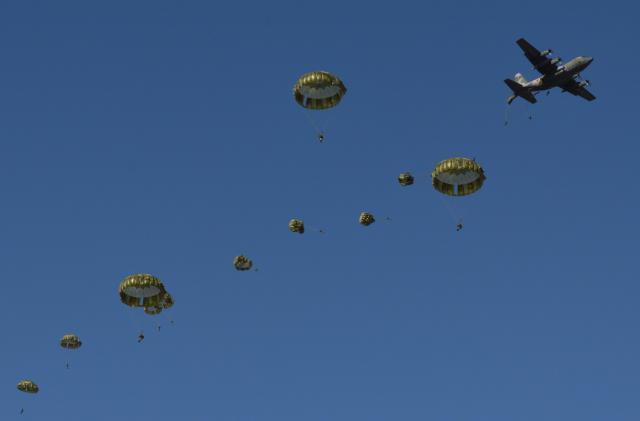 航空自衛隊のC130輸送機(右上)などから続々と降下する陸自第1空挺団の隊員たち=1月12日、千葉県の習志野演習場