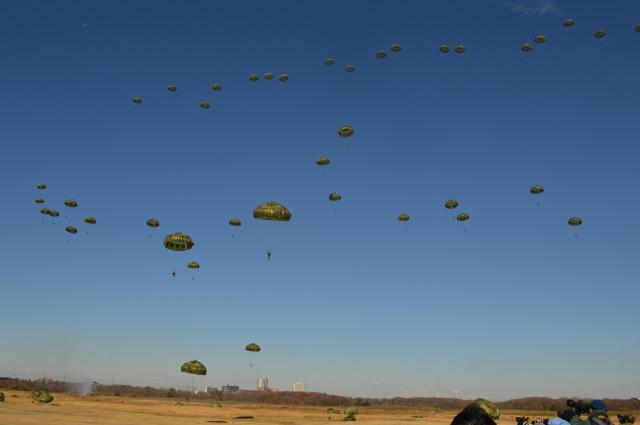 陸上自衛隊第1空挺団の空挺隊員らが次々と降下し、40ほどのパラシュートが開いた=1月12日、千葉県の習志野演習場