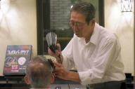接客する舩越一哉さん。都内で創業147年となる理髪店の4代目だ=渋谷区の喜多床