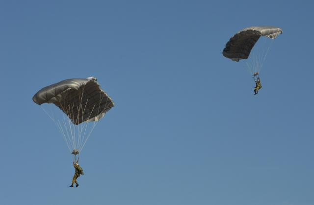 「自由降下」で高さ1200メートルからしばらく落下した後、低空でパラシュートを開いて降りてきた空挺隊員たち。パラグライダーのように操作し、より正確に着地できる=1月12日、千葉県の習志野演習場