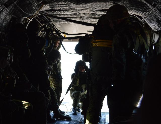 高さ340メートル。ヘリコプター後部で指示する隊員が腰を落として手招きすると、パラシュートを背負った空挺隊員6人が次々と跳び出した=1月12日、千葉県の陸上自衛隊習志野演習場の上空