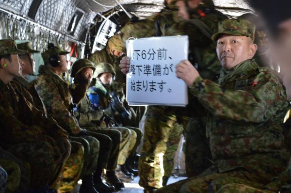 プロペラ音が激しく響くヘリコプター内で耳栓をし、パラシュート降下訓練の進行状況を示す空挺隊員=1月12日、千葉県の陸上自衛隊習志野演習場の上空