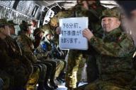 プロペラ音が激しく響くCH47ヘリコプター内で耳栓をし、第1空挺団によるパラシュート降下訓練の進行状況を示す空挺隊員=1月12日、千葉県の陸上自衛隊習志野演習場の上空。藤田直央撮影