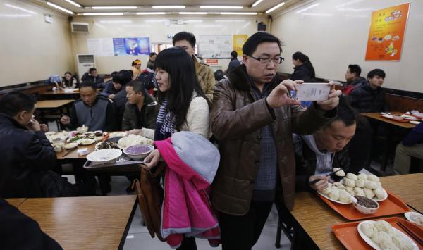 「慶豊包子舗」で記念撮影をする人々=2013年12月29日、北京