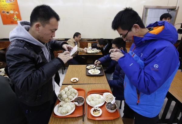 習近平主席が食べたものと同じ種類の肉まんの写真を撮っている人=2013年12月29日、北京