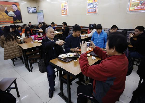 習近平主席と同じ席で座り、記念撮影をする人=2013年12月29日、北京