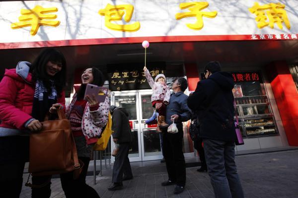習近平主席が訪問した中国のファストフードチェーン店「慶豊包子舗」。記念撮影をする人々=2013年12月29日、北京