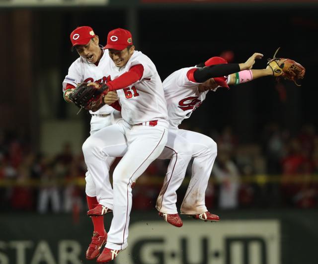 2016年、日本シリーズ初戦に勝利して体をぶつけ合う赤松真人選手(左)たち
