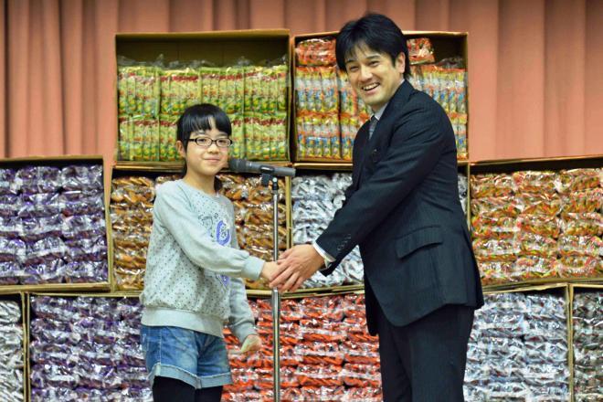 うまい棒1万本を寄贈した桐生大輔さん(右)