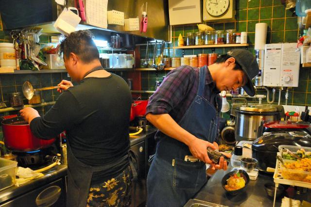 「旧ヤム邸シモキタ荘」のキッチン。客の注文を受け、手際よくカレーを盛り付けていくスタッフ=世田谷区