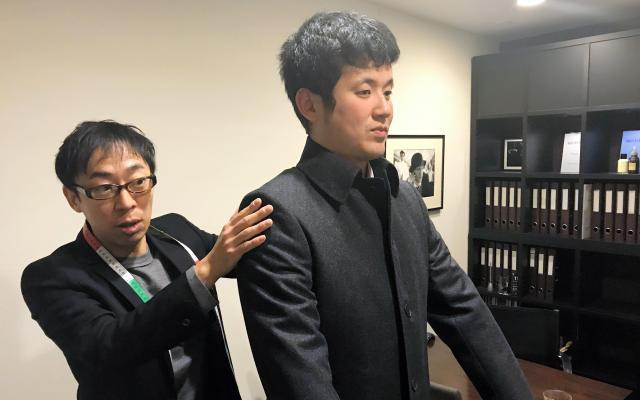 コートの試着をする石田滋一さん(右)と、吉田泰則さん=東京都港区