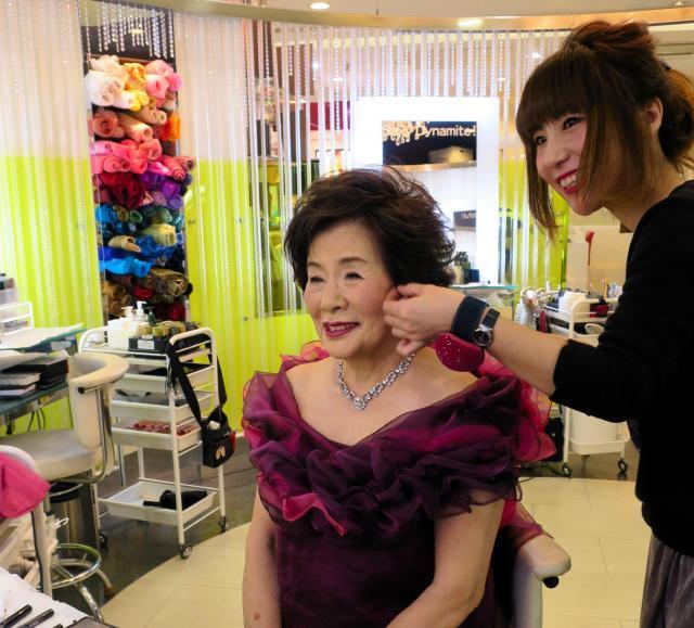 胸元も布で飾り、ちょっぴり恥ずかしそうに写真撮影に向かう78歳=千代田区のオプシス日比谷本店