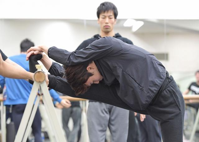 バーレッスンで柔軟をする俳優。