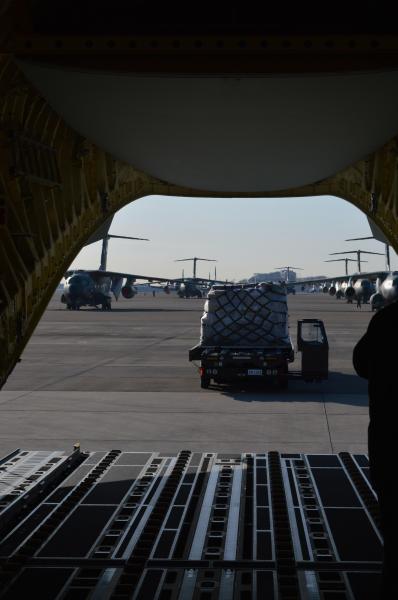 C2が空自入間基地に到着。後ろのハッチが開き、荷物を搬入しようと近づくカーゴローダーと、その向こうに並ぶC1が見える=1月31日