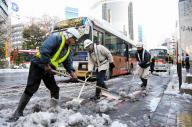 渋谷駅前のバス停で雪かきする作業員ら=2018年1月23日、東京都渋谷区、葛谷晋吾撮影