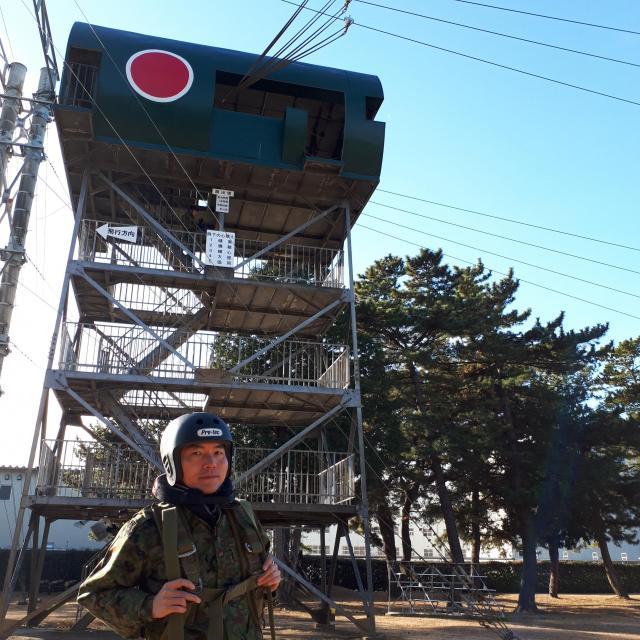 高さ11メートルの「跳出塔」と筆者(45)。パラシュート降下の基礎である跳び出し動作の訓練を体験した=1月12日、千葉県の陸上自衛隊習志野駐屯地