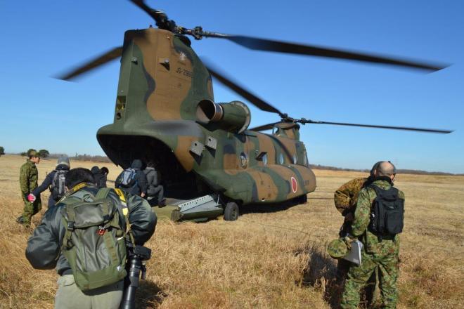 プロペラ音が響く中、陸上自衛隊のCH47ヘリコプターに乗り込む報道陣。東京タワーなみの高さからパラシュート部隊が跳び出す様子を取材する=1月12日、千葉県の陸上自衛隊習志野演習場