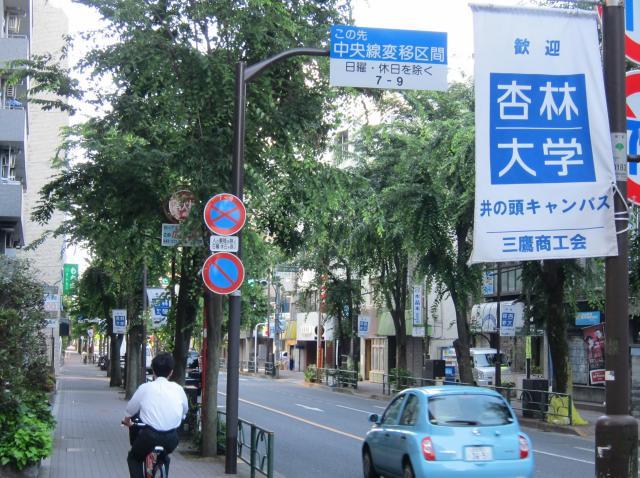 JR三鷹駅近くの通りには、「歓迎 杏林大学 井の頭キャンパス」という旗が左右に掲げられている=三鷹市、2016年6月11日