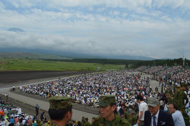 毎年恒例の陸上自衛隊による富士総合火力演習を前に満員の観客席。29倍超の抽選でチケットを手にした人や、招待された自衛隊や在日米軍の関係者ら約2万4千人が詰めかけた。左上は富士山=2017年8月27日午前、静岡県の陸自東富士演習場