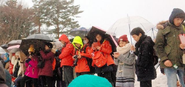ライトアップを待つ見物客たち。手には携帯やカメラなどが=1月21日午後5時1分、岐阜県白川村
