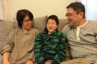 乳がん経験をした井上文子さんと家族。10歳になった天凱くんは「がんだって恥ずかしくないじゃん」という=2018年1月、東京都町田市