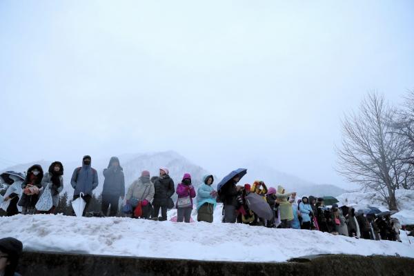 前方から見たライトアップを待つ見物客たち=1月21日午後5時15分、岐阜県白川村