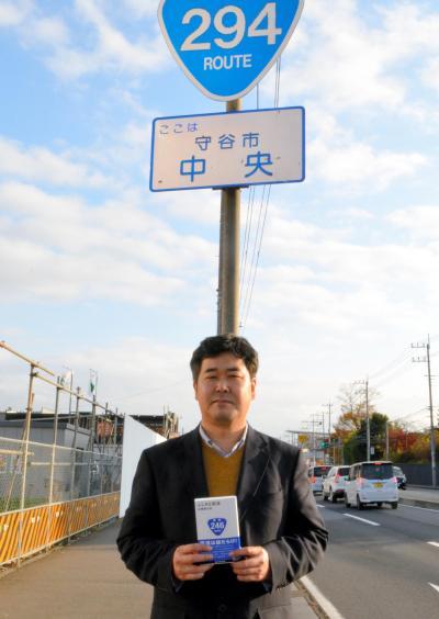 国道の標識のもとで、国道についての著書を持つ佐藤健太郎さん=茨城県守谷市