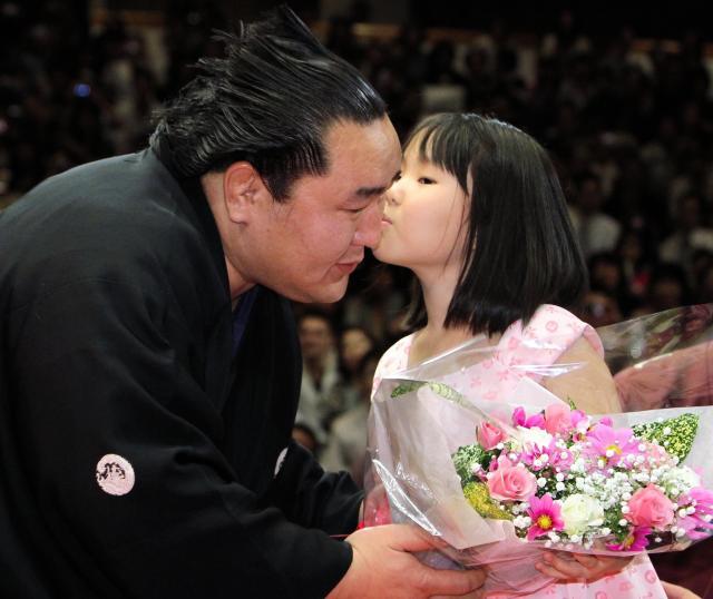 断髪式で、土俵下の長女イチンホルロちゃん(右)からキスと花束のプレゼントを受ける元横綱朝青龍=2010年10月3日