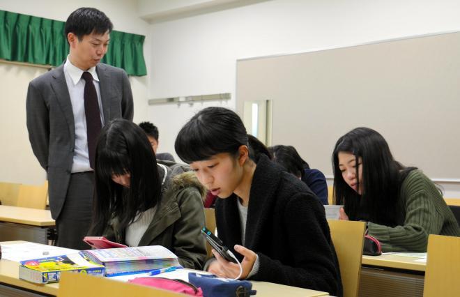 スマートフォンなどで企業の情報を調べる大学生ら=2017年12月18日