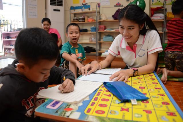 自ら立ち上げた「子どもの家」で英語を教えるスニターさん。「教えるのって難しい」と笑みを浮かべる=17年12月、ビエンチャン