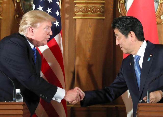 首脳会談後の共同記者会見でトランプ米大統領(左)と握手する安倍晋三首相=2017年11月6日午後、東京・元赤坂の迎賓館、代表撮影