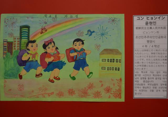 平壌の小学4年生が描いた、友達と登校する様子。胸元に赤いネッカチーフ。
