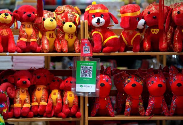 春節のための「犬のぬいぐるみ」売り場。WeChatPayのQRコード(緑色)がぶら下がっています=2018年2月8日、北京