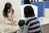 保育課の窓口で、担当者から入園内定の有無を聞く保護者=2月9日、東京都目黒区