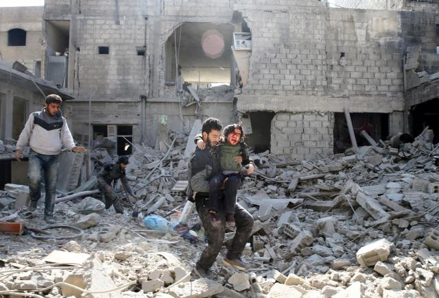 シリア・東グータ地区で、けがをした男の子を抱える男性=2月21日、ロイター