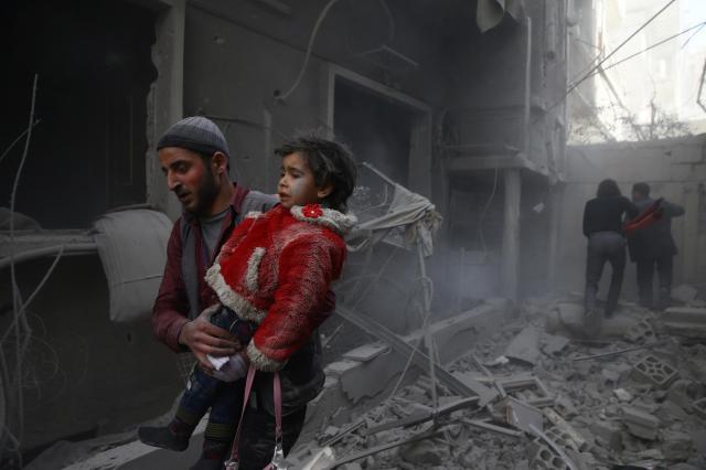 シリア・東グータ地区で、空爆によってけがをした子どもを抱える男性=2月7日、ロイター